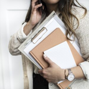 Woman carrying clipboard and business files. Blog post is about automation and business management applications.
